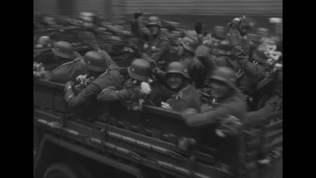 Car carrying Hitler at head of motorcade passes through guard gate crowd watching / close shot of man in crowd / man and woman in crowd giving Nazi...