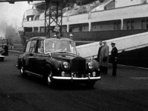 vídeos de stock, filmes e b-roll de car carrying queen elizabeth ii and prince phillip following their arrival in wales - 1960