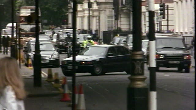 car carrying the american ambassador arrives at the us embassy in london, the day after the 9/11 attacks; 2001. policeman moving bollards. car... - one man only stock videos & royalty-free footage
