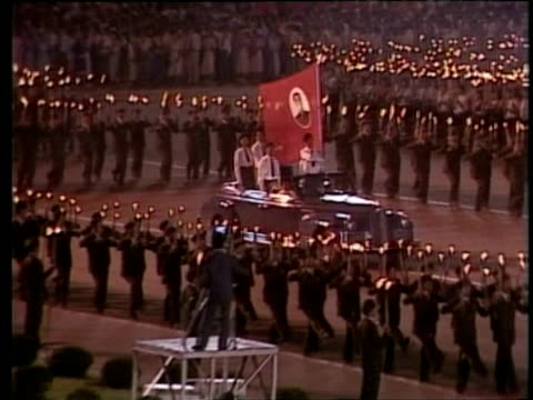 car carrying uniformed officers holding communist flag travels slowly during torch lit mass parade for leader kim il sung north korea; feb 88 - communist flag stock videos & royalty-free footage