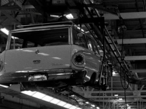 stockvideo's en b-roll-footage met car chassis is lowered onto a production line at a car factory in the usa. - chassis