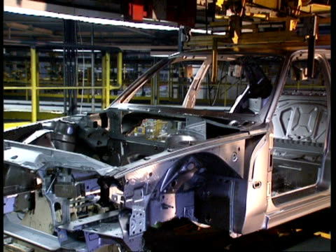 vidéos et rushes de ms car chassis lowered and rotated on machine in factory, tilt down - machinerie