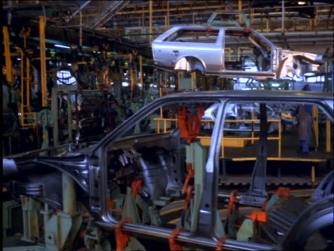 car chassis moving past camera on assembly line in volkswagen factory / workers in background / brazil - automobilindustrie stock-videos und b-roll-filmmaterial