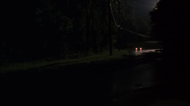 ms car coming toward camera on rural road lined with trees / unspecified - headlight stock videos & royalty-free footage