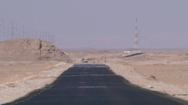 ws car coming towards on road / el kharga, egypt - land vehicle stock videos & royalty-free footage
