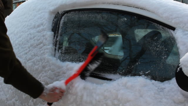 Car covered in snow, brushing it off with ice scraper