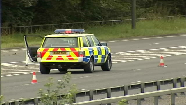 surrey cobham a3 ext traffic along a3 past overturned cars at roadside with police cars in attendance - コブハム点の映像素材/bロール