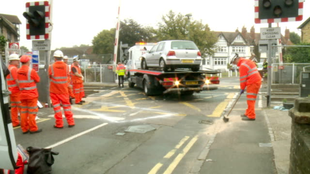 car crashes into train on level crossing in datchet; england: berkshire: datchet: ext sign 'road closed' in road two police officers car on back of... - road closed englisches verkehrsschild stock-videos und b-roll-filmmaterial