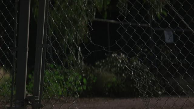 A car crashes through a chain link fence.