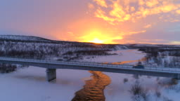 AERIAL: Car crossing bridge above icy river in scenic winter landscape at sunset