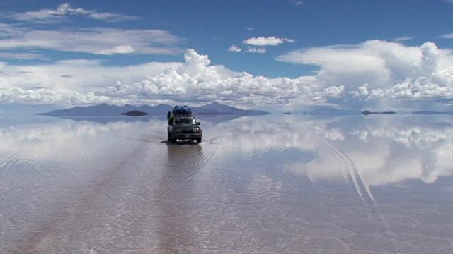 car crossing the vast salt desert covered with a mirror like film of water after rain. bolivia, salar de uyuni - ウユニ塩湖点の映像素材/bロール