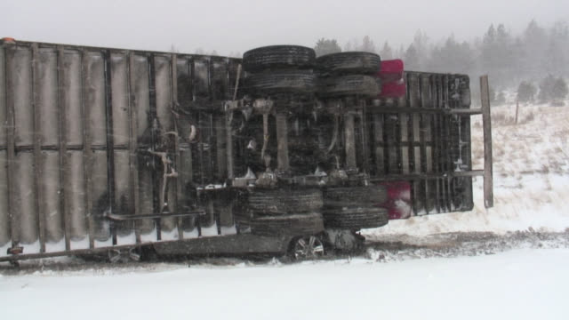 Car crushed beneath overturned semi-truck during snow storm.