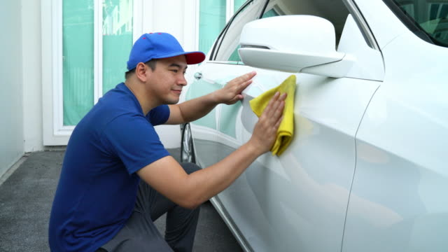 Car detailing, Man in blue uniform clean a white car in hand holding a microfiber washing large car.
