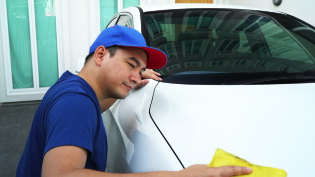 Car detailing, Man in uniform clean a white car in hand holding a microfiber washing large car