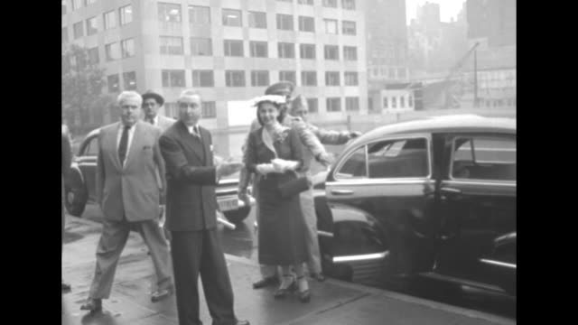car door opens and general matthew ridgway and his wife penny step onto sidewalk greeted by two men the couple stops briefly in the rain for a photo... - matthew b. ridgway stock-videos und b-roll-filmmaterial