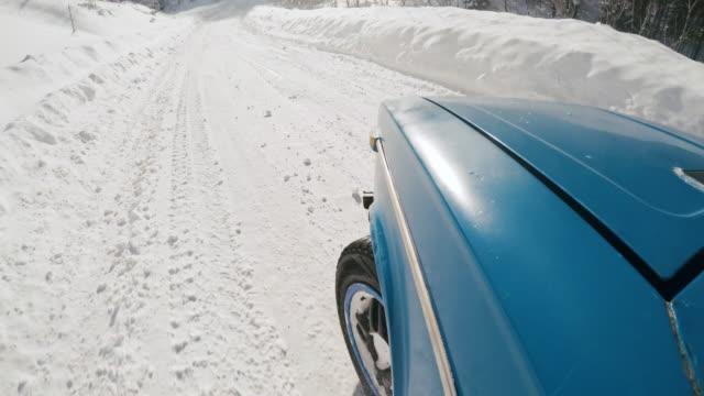 car drifting and speeding along snowbound road - 横滑り点の映像素材/bロール