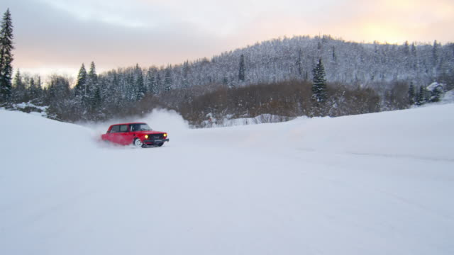vidéos et rushes de car drifting on snowy road and stopping before camera - neige fraîche