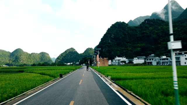 car drive on road with rice fields and village,guizhou,china. - rice paddy stock videos & royalty-free footage