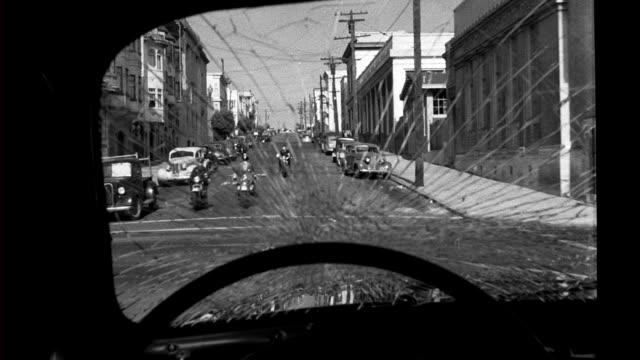 POV car driver cracked broken windshield driving though city streets POV car driver cracked broken windshield on January 01 1950