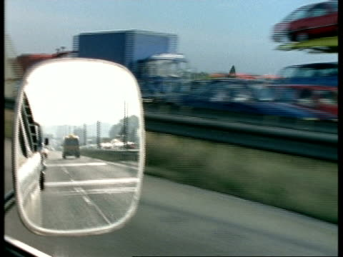 POV of car driver looking in rear view mirror as  travels along motorway, England