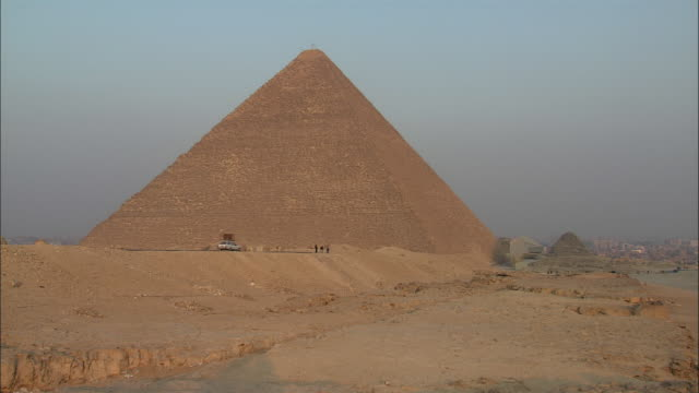 a car drives across the desert past a towering egyptian pyramid. - pyramide bauwerk stock-videos und b-roll-filmmaterial