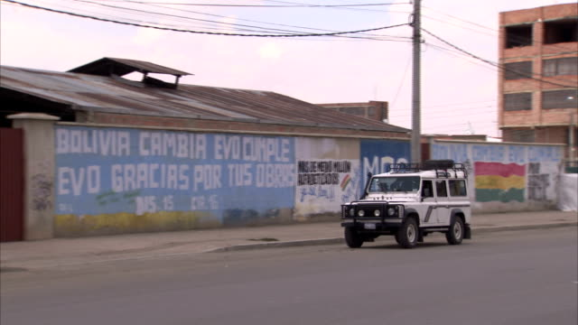 a car drives along a city street past walls spray-painted with political messages supporting bolivian president evo morales. available in hd. - evo morales stock videos & royalty-free footage