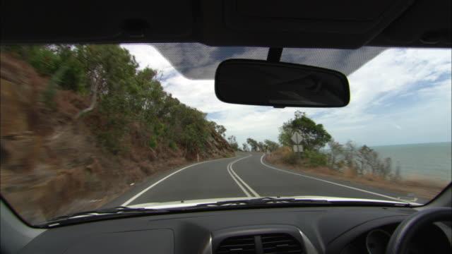 a car drives along a coastal highway. - windschutzscheibe stock-videos und b-roll-filmmaterial