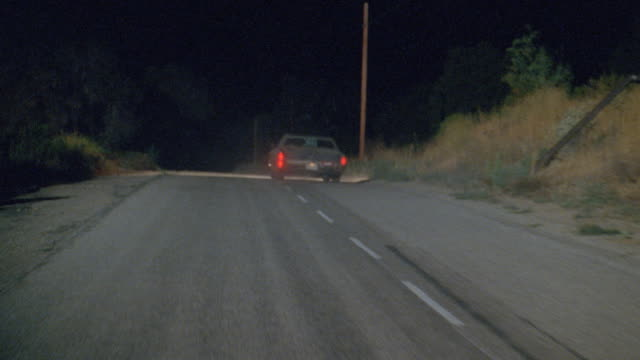 a car drives along a country road at night. - country road stock videos & royalty-free footage