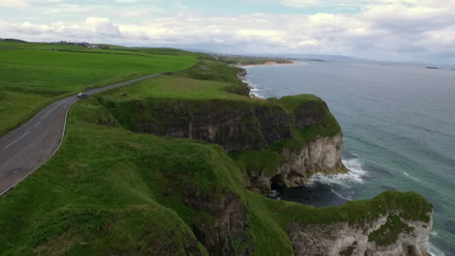 a car drives along a stretch of green, rugged county antrim coastline, northern ireland. - northern ireland stock videos & royalty-free footage