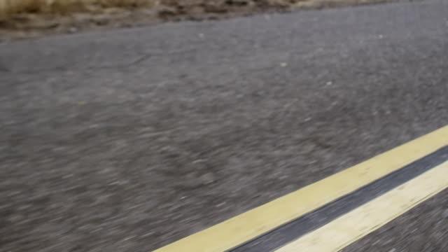 Car drives along double yellow line closeup