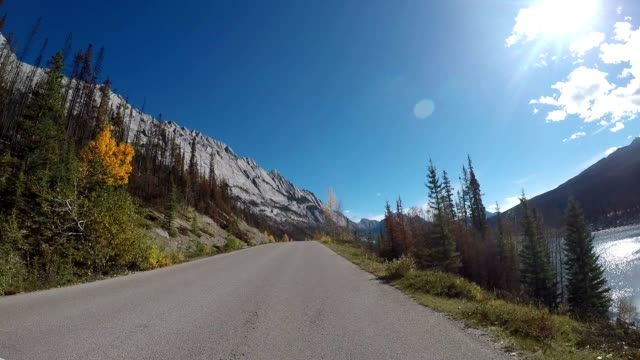 Car drives along lake stunning lake road POV