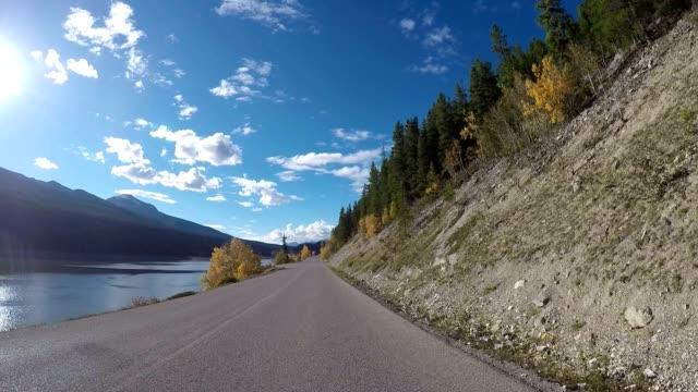 Auto rijdt langs meer prachtige lake road POV