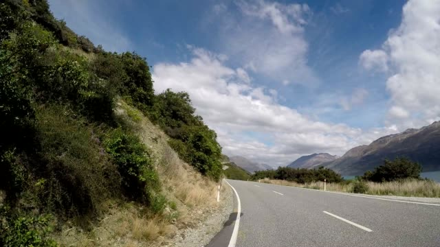car drives along spectacular road above lake pov - majestic stock videos & royalty-free footage