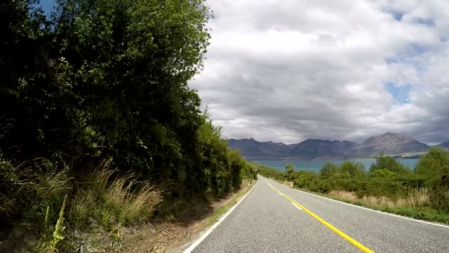 car drives along spectacular road above lake pov - queenstown stock videos & royalty-free footage