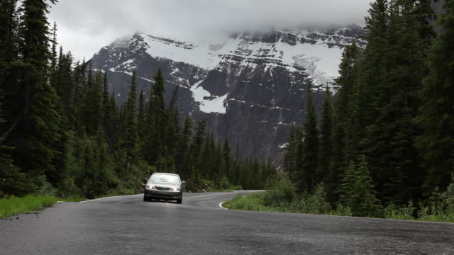 Car drives along twisty mountain road below snowy mtn