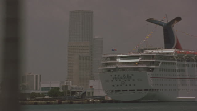 stockvideo's en b-roll-footage met a car drives by a miami harbor with high rise buildings and a docked cruise ship in the background. - rondrijden