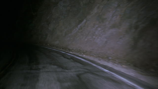 a car drives down a curving highway at night. - hill stock videos & royalty-free footage