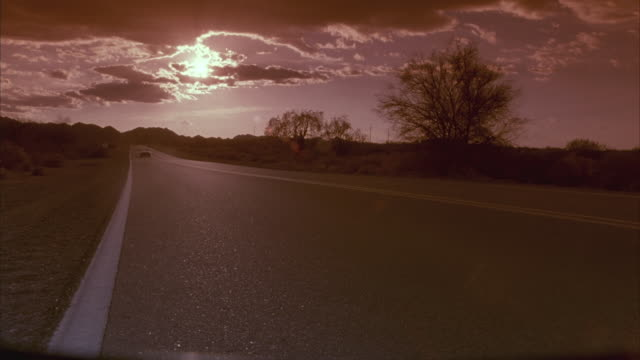 A car drives down a desert road.