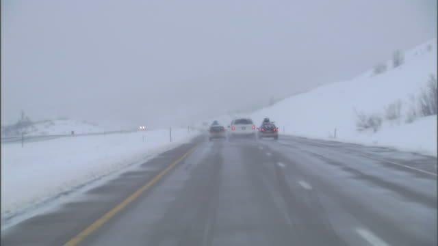 a car drives down a snowy and wet highway. - utah stock videos & royalty-free footage