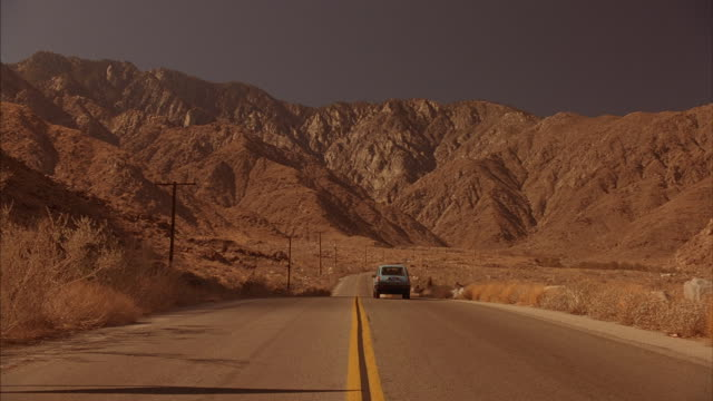 A car drives down a two-lane road towards mountains in the distance.