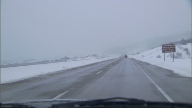 a car drives down a wet and snowy highway. - utah stock videos & royalty-free footage