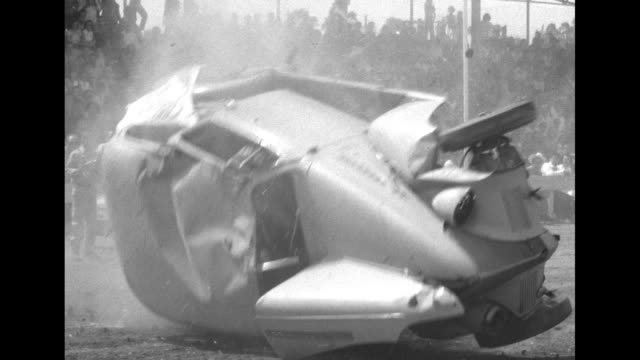 vidéos et rushes de car drives down track and crashes headon into other car / car drives off side of ramp and rolls over / attendants pushing car lying on its side back... - rouler ou dérouler