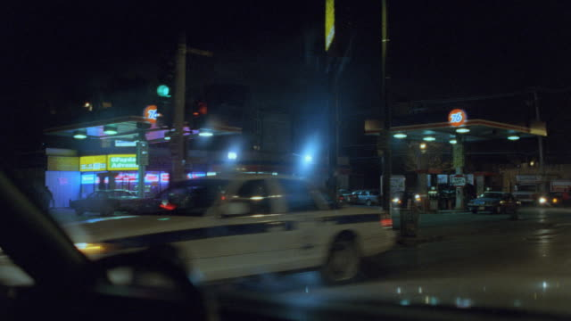 a car drives on a chicago street at night. - chicago illinois stock videos & royalty-free footage