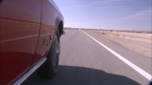 a car drives on a desert road. - reifen stock-videos und b-roll-filmmaterial