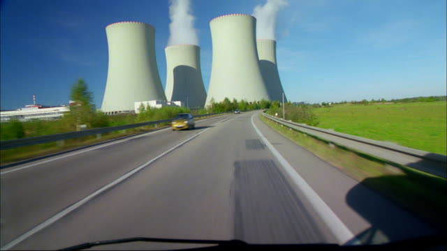 a car drives on a road toward a nuclear power plant. - nuclear power station stock videos & royalty-free footage