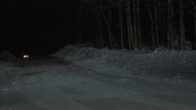 a car drives on a snow covered road at night. - 30 seconds or greater stock videos & royalty-free footage