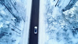 Car drives on a winter road. Winter road, trees and bushes covered with snow.