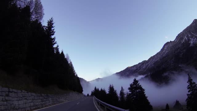 Auto fahren Sie auf der mountain road über cloud POV