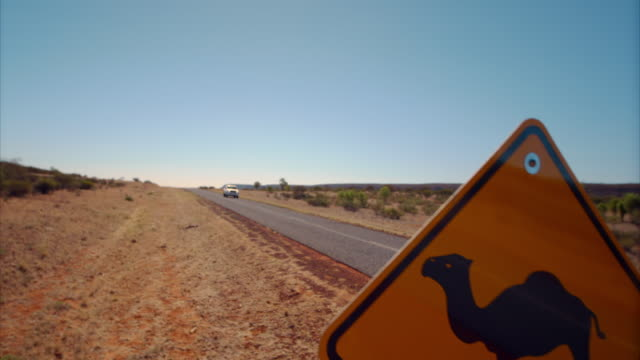 A car drives past a camel road sign in the Northern Territory of Australia.