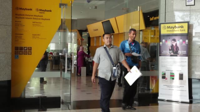 A car drives past a Maybank Islamic Bhd bank branch in Kuala Lumpur Malaysia on Wednesday March 2 Customers use automated teller machines at a...